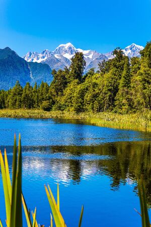 Lake Matheson is glacial lake. Mountain peaks covered with snow. Glacial lake surrounded by forests. South Island of New Zealand. The concept of ecological, active and photo tourism