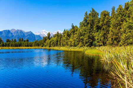 The famous lake Matheson reflects Mount Cook and Mount Tasman. Lake Matheson is picturesque glacial lake in the South Island of New Zealand. The concept of ecological, active and photo tourism
