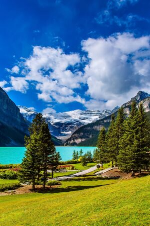 The lake is surrounded by high mountains and forests. Glacial Lake Louise in Canadian Rockies. The embankment with green lawns and flower beds. The concept of ecological and photo tourism