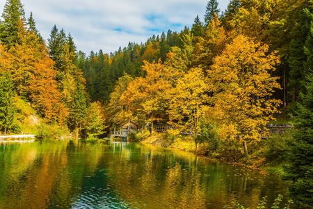 Fantastically beautiful autumn forests are reflected in the quiet lake Lago de Fusine. Easy ripples on the lake. Flood after rain. Concept of cultural and ecological tourism