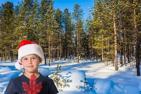 Handsome boy with red maple leaf smiling. Lapland. Ski track road in the snow-covered coniferous forest. The concept of extreme and active tourism Banco de Imagens