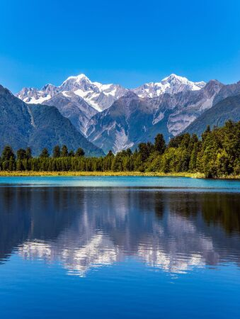 The forests and Mount Cook and Mount Tasman. Magnificent snow-capped mountains surround the smooth, cold waters of Lake Matheson.The concept of ecological, active and photo tourism Stok Fotoğraf