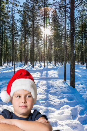 Lapland. Frosty winter day in the Arctic. Handsome boy in red Santa Claus hat smiling. The snow-covered coniferous forest. The concept of extreme and active tourism