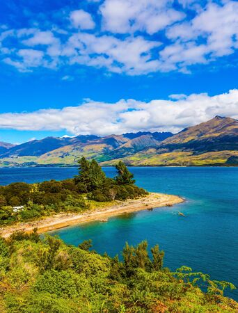 The turquoise deep lake Wanaka in New Zealand. Magical journey to the ends of the earth. South Island. Concept of active, ecological and photo tourism