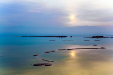 The sun is reflected in the water of the sea. Winter foggy dawn. Excess salt appears on the surface of the water. Dead Sea, Israel. Concept of ecological, medical and photo tourism