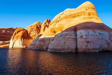 Sunset. The Colorado River and Antelope Canyon. Grandiose cliffs - red sandstone outcroppings. Tour on a tourist boat on an artificial reservoir Lake Powell. Concept of active and photo tourism