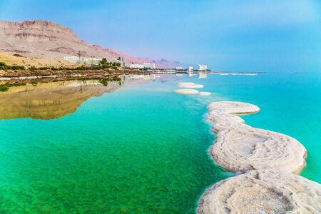 Israel. Early morning at the resorts of the Dead Sea. Azure sea water is full of healing salts. Small islets and path of salt in the water. Concept of ecological, medical and photo tourism Stock Photo