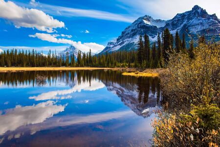 The mountains, forests and lake in the Rockies of Canada. Clouds reflected in the smooth water of the lake. Autumn trip to the Rockies of Canada. The concept of active, eco and photo tourism Stok Fotoğraf