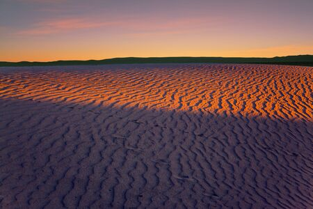 Orange sunset in the desert. Mesquite Flat Sand Dunes, California. The gentle slopes of the sand dunes are rippled by the wind. Concept of active, ecological and photo tourism