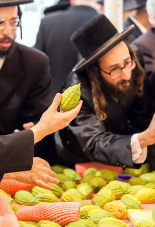 JERUSALEM, ISRAEL - SEPTEMBER 20, 2018: Pre-holiday bazaar in Jerusalem on the eve of Sukkot. Religious young Jews choose etrog. The concept of religious, ethnographic and photo tourism