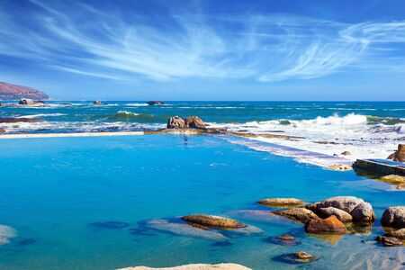 Coastline, beach and stones. Cape Town at the foot of Table Mountain. Promenade and beach in fabulous port city. The concept of active, exotic and photo tourism Фото со стока - 134868212