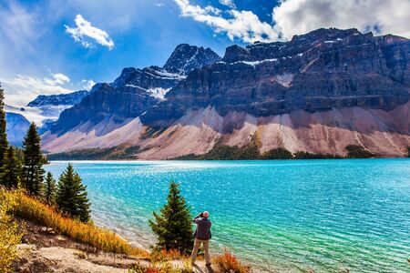 The Majestic Rockies of Canada. A gray-haired tourist photographs a grandiose landscape. Lake Bow is surrounded by cliffs and glaciers. The concept of active, environmental and photo tourism Фото со стока - 134868808