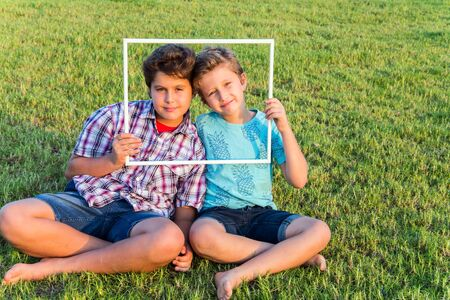 Background - green summer lawn. Concept - portrait and advertising photo. Two cute boys - brothers smiling, looking through a white frame
