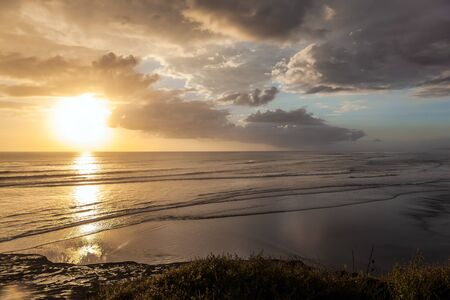 Sunset. The Muriway Beach, New Zealand. The magnificent nature of the Southern hemisphere. The concept of active, environmental and photo tourism 版權商用圖片 - 134871848