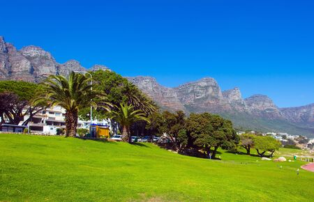 Promenade and beach in fabulous port city. The magnificent famous Table Mountain and Cape Town at its foot. The concept of active, exotic and photo tourism