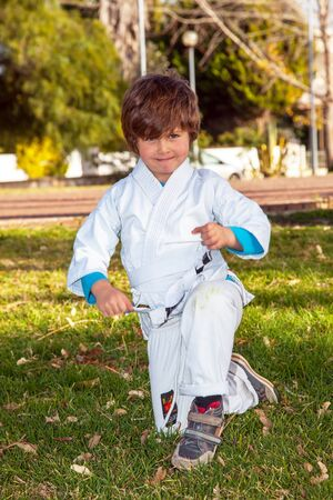 Charming boy in a white kimono in a park practices judo. Palm trees and green grass in childrens park. Concept - photo advertising, children, sports