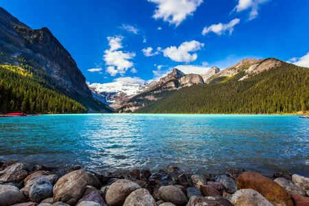 Glacial Lake Louise - the lake with azure water is surrounded by forests and mountains. Red canoes for tourists are moored to the coast. Rocky Mountains. The concept of active and photo tourism Archivio Fotografico