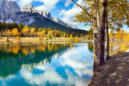 Cumulus clouds reflected in the smooth water of the lake. Lush autumn in the Canadian Rockies. Outskirts of Canmore. The concept of active, ecological and photo tourism