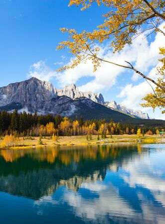 Lush autumn in the Canadian Rockies. Cumulus clouds reflected in the smooth water of the lake. Outskirts of Canmore. The concept of active, ecological and photo tourism 스톡 콘텐츠