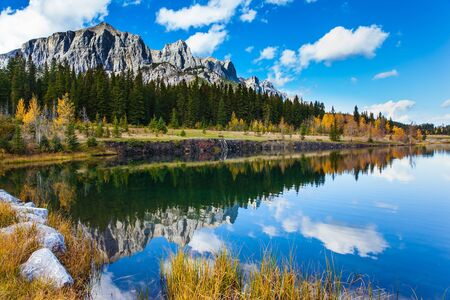 Bright autumn forest is reflected in the smooth water of the lake. The city of Canmore. Three Sisters Mountain in Canadian Banff Park. The concept of active, ecological and photo tourism