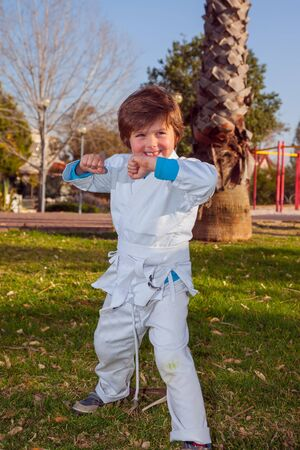 Handsome boy in a white kimono practices judo in a park. Background - children's park, palm trees and green grass. Concept - photo advertising, children, sports