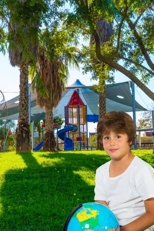Charming boy with a globe. Background - Cosy and safe children s playground with a variety of multicolored attractions. The concept of physical and mental development of children 写真素材
