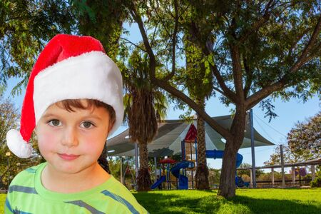Handsome boy in Santa Claus hat smiling. Children s playground with a multicolored attractions. The concept of physical and mental development of children 写真素材