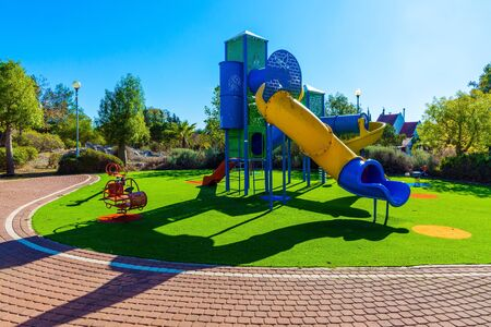 Safe and cozy children's playground with a variety of colorful rides. Outdoor sunny lawn for children. Bright warm sunny morning. The concept of physical and mental development of children Zdjęcie Seryjne
