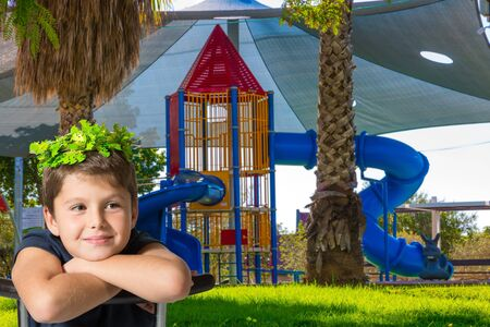 Beautiful boy in wreath of leaves smiling. Children s playground with a multicolored attractions. The concept of physical and mental development of children