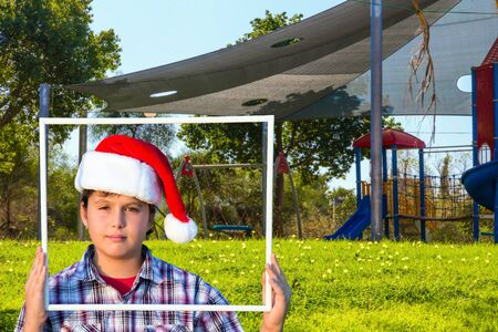 Boy in Santa Claus hat smiling holding a frame in his hands. Children s playground with a multicolored attractions. The concept of physical and mental development of children 写真素材
