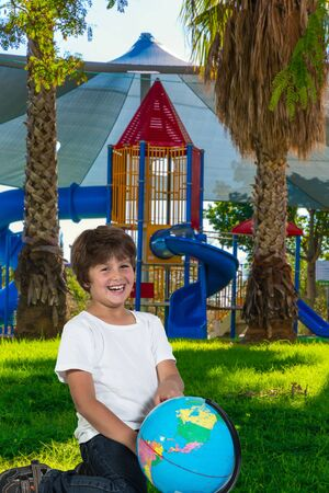Handsome and charming boy laughs cheerfully, holding a globe in his hands. Cosy and safe children s playground with attractions. The concept of physical and mental development of children 写真素材