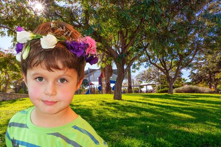 Beautiful boy in a flower wreath smiling. Sunny morning in shady park. Great and safe playground for children. The concept of physical and mental development of children