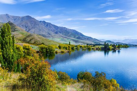 Magic South Island, New Zealand. Emerald-colored deep lake water and grassy lawns. The picturesque lake Dunstan near the town of Cromwell. The concept of ecological and photo tourism