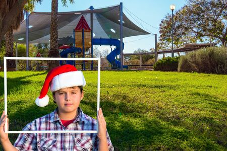 Handsome boy in Santa Claus hat smiling holding a frame in his hands. Children s playground with a multicolored attractions. The concept of physical and mental development of children 写真素材
