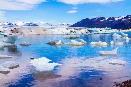 Kalter, klarer Julitag. Bizarre Eisberge und schwimmende Eisschollen spiegeln sich im glatten kalten Wasser der Lagune. Die Lagune Jokulsaurloun. Island. Das Konzept des Öko-, Nord- und Fototourismus Standard-Bild