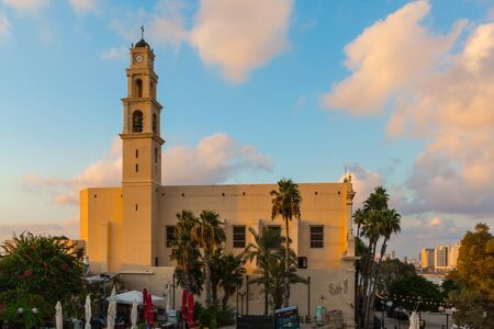 Old Yaffo - one of the most ancient cities of the world. Bell tower of catholic cathedral. Sunset in Tel Aviv. Concept active, informative and photo of tourism Foto de archivo