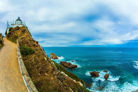 The white building of the lighthouse looks spectacular on a high cape. New Zealand. Nugget Point Lighthouse. Direct path leads to the lighthouse. The concept of active, environmental and photo tourism 스톡 콘텐츠