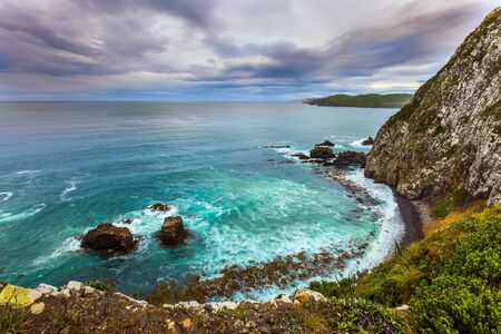 New Zealand. The picturesque coast of the Pacific Ocean near Nugget Points. Sunset sky portends a storm. Big stones along the shore. The concept of active, environmental and photo tourism