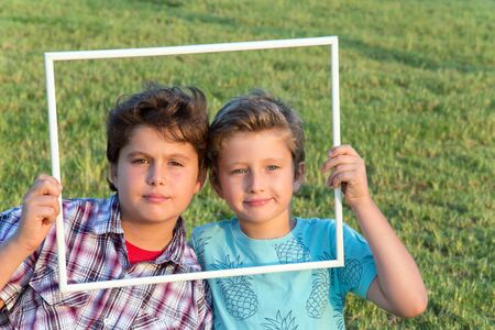 Two adorable boys smiling cheerfully, looking at viewers through a white frame.  Background - green summer lawn. Concept - portrait and advertising photo Standard-Bild