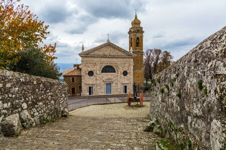 The small town of Montalcino. Beautiful facade and bell tower of the church. Cloudy autumn day in Tuscany. The concept of cognitive, active and photo tourism