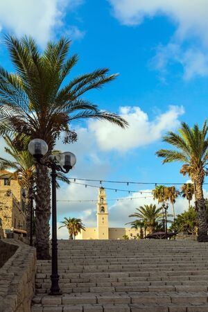 Sunset. Old Yaffo - one of the most ancient cities of the world. The wide stone erased steps of the ancient city. Century masonry walls. Concept active, informative and photo of tourism
