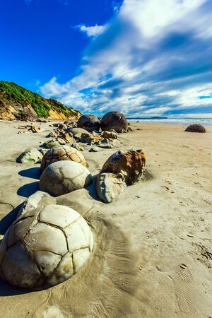 Series of mysterious round boulders Moeraki and their shattered remnants on a sandy beach. Popular tourist attraction. New Zealand. Low tide in the Pacific. The concept of exotic and ecological touri