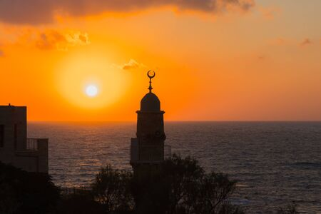 Round tower crowned with a crescent is a Muslim minaret. Old Yaffo - one of the most ancient cities of the world. The sun plunges into the Mediterranean Sea. Concept active and photo of tourism