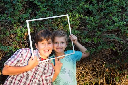 Two adorable boys smiling cheerfully, looking at viewers through a white frame.  Background - green summer park. Concept - portrait and advertising photo