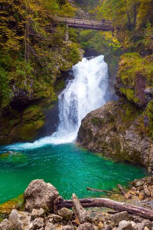 Roaring foamy rapids and waterfalls. The mountain river. On the slopes of the gorge laid wooden walkways with railings and bridges. Slovenia. Vintgar gorge. The concept of active and photo tourism Stock Photo