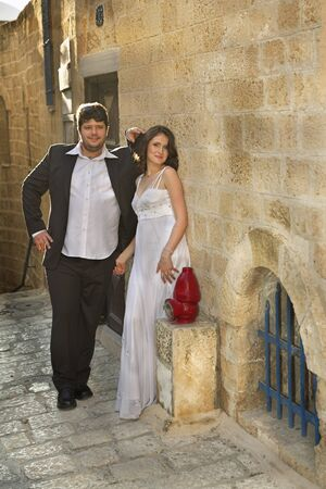 The beautiful, happy groom and the bride on prewedding walk in ancient to port. Imagens