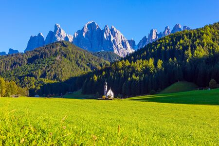 Italy, Tyrol. Small white church with a bell among green lawns on the sunset. The most beautiful village in the world, Santa Maddalena in the Val di Funes Valley.