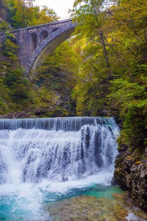 Powerful rumbling waterfall on a mountain river. Picturesque old bridge over the Vintgar mountain gorge. Slovenia. The concept of active and photo tourism