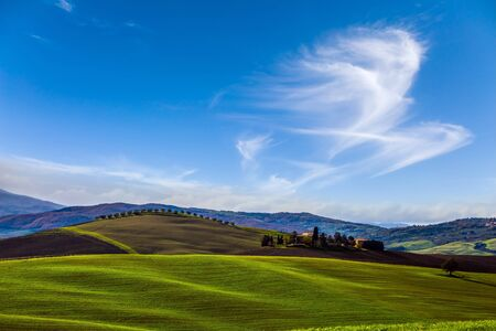 Agritourism. Rural farms and  picturesque hills of Tuscany after harvest. Light clouds over Tuscany hills. Beautiful Italy.