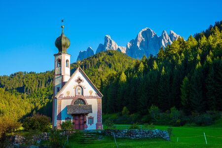 The Val di Funes Valley. Majestic Dolomites. Beautiful picturesque church and bell tower on the sunset. Tyrol, Italy.